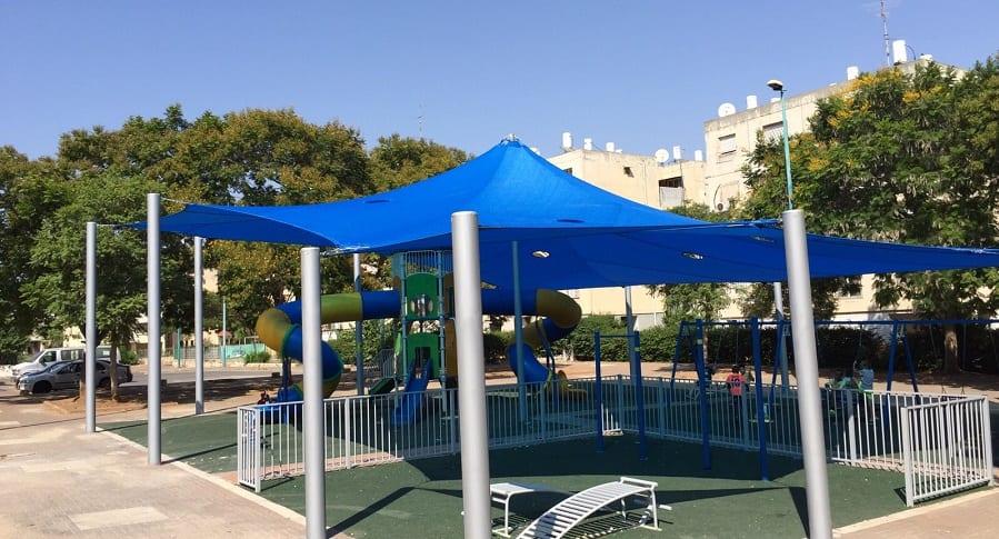רשת הצללה בצבע כחול עם עמודים במתחם משחקים וכושר